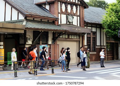 TOKYO, JAPAN - June 5, 2020: People at a crosswalk in front of the old and now closed Harajuku Station. People are wearing face masks during the coronavirus outbreak.