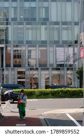 TOKYO, JAPAN - June 5, 2020: A sidestreet and main street in Tokyo's Omotesando area on a sunny day. People wear face masks during the  coronavirus outbreak.