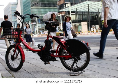 TOKYO, JAPAN - June 9, 2018: An e-bike belonging to Toyko's public bicycle sharing scheme parked on a sidewalk outside a store in Nihonbashi, central Tokyo.