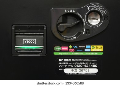 TOKYO, JAPAN - March 10, 2019: Detail of a drinks vending machine with slots for coins and banknotes and the logos of IC cards which the machine accepts.