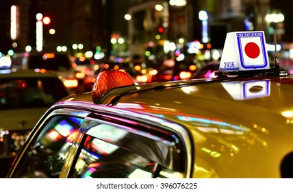 TOKYO, JAPAN - MARCH 12, 2016: Taxi with Japanese Flag logo in Tokyo traffic at night.