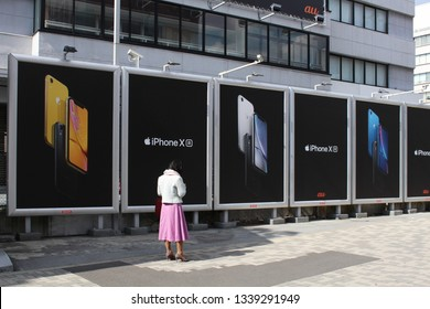 TOKYO, JAPAN - March 14, 2019: A line of billboards advertising iphones and cellphone service provider au in the Tokyo's Omotesando area.