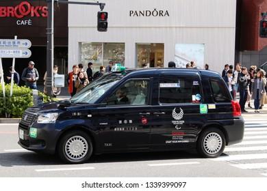TOKYO, JAPAN - March 14, 2019: A Toyota JPN Taxi with Tokyo Olympic 2020 logo going through Tokyo's Omotesando area.