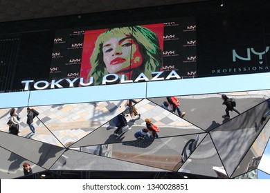 TOKYO, JAPAN - March 14, 2019: Section of the front of Tokyu Plaza Omotesando shopping center with an NYX advert playing on a large screen and the street below relected in kaleidoscopic mirrors.