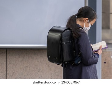 TOKYO, JAPAN - MARCH 15TH, 2019. School girl wearing mask reading a book at Shinjuku Railway station in the morning.