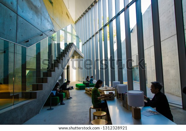 Tokyo, Japan - March 18 2016: Girls reading in the museum of 21 21 Design Sight designed by Tadao Andoin Tokyo