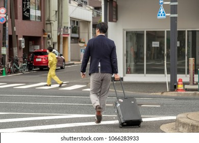TOKYO, JAPAN - MARCH, 2018: Businessman with luggages crossing road. Rear view of a businessman pulling suitcase.