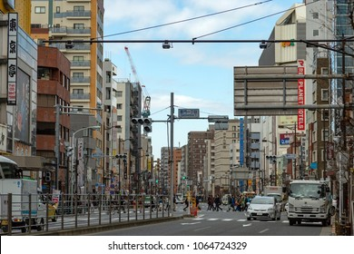 TOKYO, JAPAN - MARCH, 2018: Tokyo streets scene with pedestrians and car traffic. In Japan there is left-hand traffic.