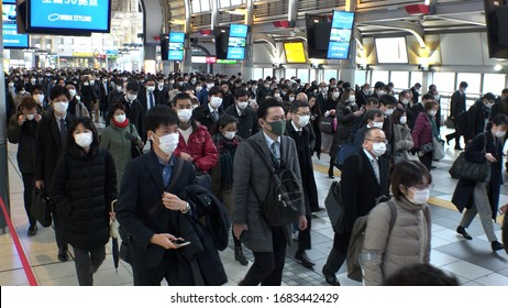 TOKYO, JAPAN - MARCH 2020 : Crowd of people walking at Shinagawa station in busy morning rush hour. Many commuters going to work. People wearing surgical mask to protect from Coronavirus(COVID-19).