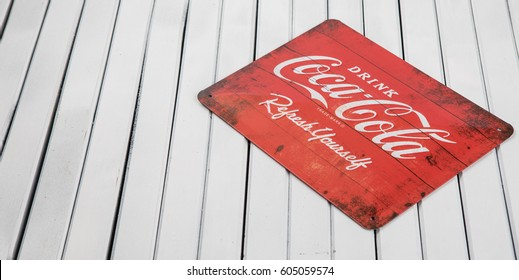 TOKYO, JAPAN - MARCH 20TH, 2017. Vintage Coca Cola metal sign over wooden background., Coca-Cola  is a carbonated soft drink  produced by The Coca-Cola Company.