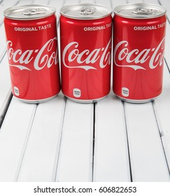TOKYO, JAPAN - MARCH 20TH, 2017. Coca Cola can drinks over wooden background., The carbonated soft drink  is produced by The Coca-Cola Company.