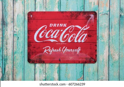 TOKYO, JAPAN - MARCH 21ST, 2017. Vintage Coca Cola metal sign over wooden background., Coca-Cola is a carbonated soft drink produced by The Coca-Cola Company.