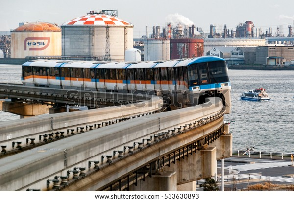Tokyo, Japan - March 22, 2015: Series 1000 train on the Tokyo Monorail Haneda Airport Line comes round a bend with industrial Tokyo Bay in the background