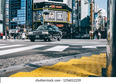 TOKYO, JAPAN - MARCH 23, 2018: View of road with a taxi car and people in Shinjuku. Shinjuku is popular area that tourists have to go.
