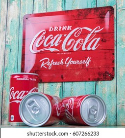 TOKYO, JAPAN - MARCH 23RD, 2017. Coca Cola can drinks and vintage metal sign over wooden background., The carbonated soft drink  is produced by The Coca-Cola Company.