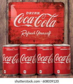 TOKYO, JAPAN - MARCH 24TH, 2017. Coca Cola can drinks over wooden background., The carbonated soft drink  is produced by The Coca-Cola Company.