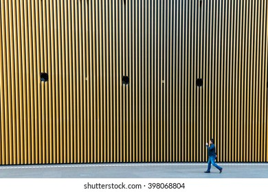 Tokyo, Japan - March 27 2016:Pedestrian walking in front of striped pattern wall at Tokyo International Forum in Tokyo, Japan.