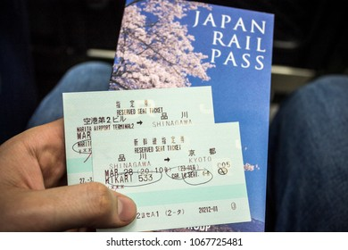 TOKYO, JAPAN - March 28, 2015: Hand holding a Japan Rail Pass with two tickets for the Japanese JR train Shinkansen network from Shinagawa to Kyoto