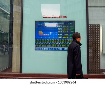 TOKYO, JAPAN - MARCH 28, 2019: A salaryman walks pass a screen displaying TOPIX stock index prices in front of a Daiwa Securites Group office, Shibuya City. Travel and finance.