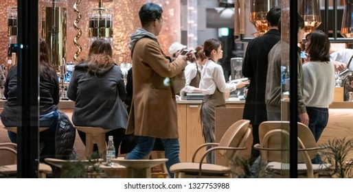 TOKYO, JAPAN - MARCH 2ND, 2019.  Customers and baristas at the Starbucks Reserve Roastery at night. The newly opened establishment is the 5th of such outlet and is the largest in the world.