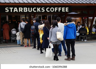 TOKYO, JAPAN - March 3, 2018: A long line of customers outside a busy Starbucks branch in Tokyo's Ueno Park.