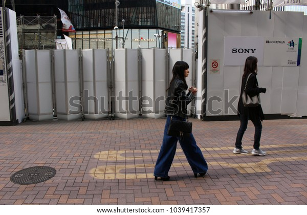TOKYO, JAPAN - March 3, 2018: People passing the temporary fence around the site of the now-demolished Sony Building and future Sony Park in Ginza.Tokyu Plaza shopping complex is in the background.