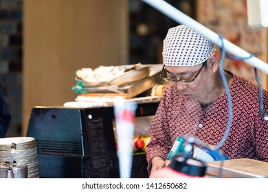 Tokyo, Japan - March 30, 2019: Outer market street in Tsukiji near Ginza with food vendor man closeup using blowtorch