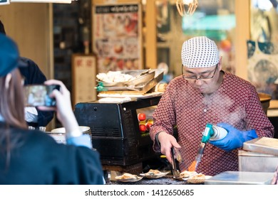 Tokyo, Japan - March 30, 2019: Outer market street in Tsukiji near Ginza with food vendor man using blowtorch and woman taking picture with phone