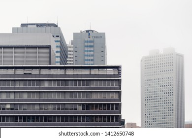 Tokyo, Japan - March 30, 2019: Shinjuku modern skyscraper building with contemporary glass office on cloudy day with sign in Japanese for Kogakuin University of Technology & Engineering