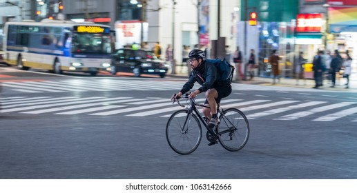 TOKYO, JAPAN - MARCH 30TH, 2018. Man riding a bicycle in the middle of Shibuya street at night.