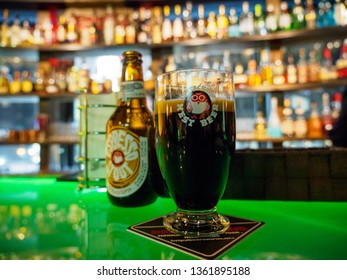 TOKYO, JAPAN - MARCH 31, 2019: Wide closeup detail of a glass of Hitachino Nest espresso stout beer nest to a bottle on a bar counter, liqour on the shelves. Travel and party.