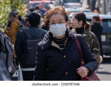 TOKYO, JAPAN - MARCH 5TH, 2019. Elderly Japanese woman wearing mask walking in the street of Nakameguro.