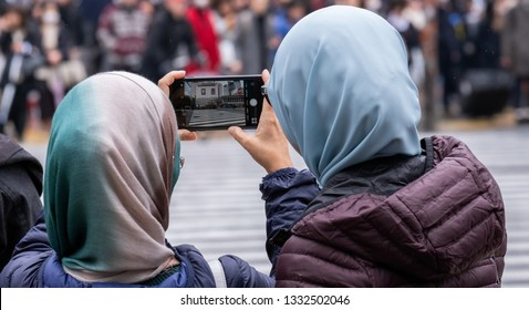 TOKYO, JAPAN - MARCH 7TH, 2019. Malaysian muslim female tourists in hijab taking pictures at Shibuya pedestrian crossing.