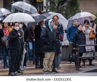 TOKYO, JAPAN - MARCH 7TH, 2019. Pedestrian crowd with umbrella waiting to cross the famous Shibuya crossing during a rainy day.