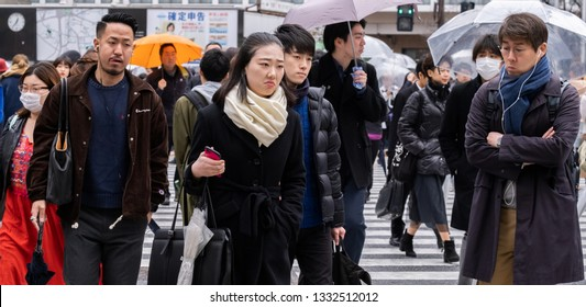 TOKYO, JAPAN - MARCH 7TH, 2019. Pedestrian crossing the famous Shibuya crosswalk during a rainy day.