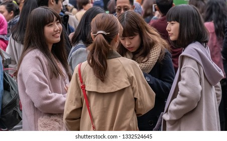 TOKYO, JAPAN - MARCH 7TH, 2019. A group of Japanese girls hanging out at Hachiko square in Shibuya.