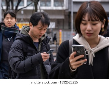 TOKYO, JAPAN - MARCH 7TH, 2019. Girl with her smartphone at Shibuya pedestrian crossing.