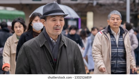 TOKYO, JAPAN - MARCH 7TH, 2019. Elderly man with a hat walking across the Shibuya crossing.