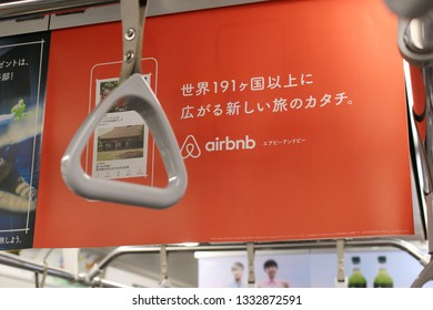TOKYO, JAPAN - March 8, 2019: A hanging strap and a poster advertising airbnb inside a Tokyo subway train.  Focus is on the advert.