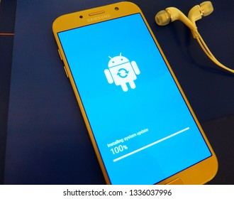 Tokyo, Japan. March 9, 2019 - smartphone system update installation complete. android robot close up on smartphone blue screen.
