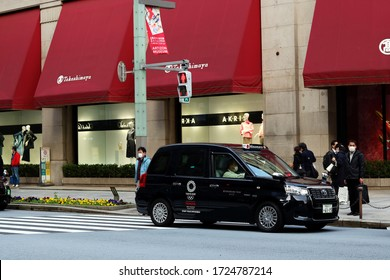 TOKYO, JAPAN - March 9, 2020: Taxi & people in front of Nihonbashi's Takashimaya store. The people wear face masks due to the coronavirus outbreak. The car is Toyota JPN Taxi with Tokyo Olympic logo.