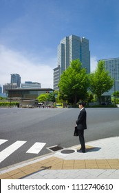 Tokyo, Japan - May 11 2018 : One young man dressed in black waiting alone, patiently at an empty crossroad in front of the Prime Minister's Official Residence with high office buildings in background