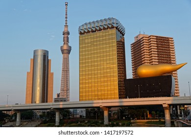 TOKYO, JAPAN, May 11, 2019 : Asahi Beer Hall and Asahi Flame seen from the district of Asakusa, on the other bank of Sumida river, with Tokyo tower.