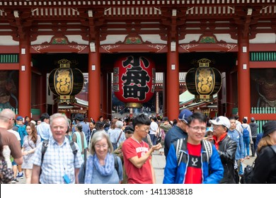 TOKYO, JAPAN - MAY 12, 2019 : Tourists walking through The Kaminarimon (Thunder Gate), the outer gate of Sensoji Temple. It's symbol of Asakusa district, Tokyo, Japan.