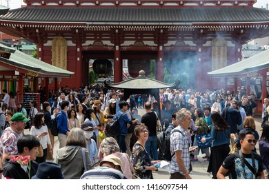 TOKYO, JAPAN - MAY 12, 2019 : Unidentified people covering themselves with smokes from the large incense burner at the Sensoji Temple. Asakusa Temple is one of Tokyo Landmark located in Asakusa.