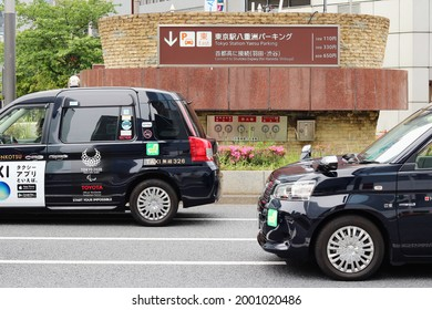 TOKYO, JAPAN - May 12, 2021: A pair of taxis on a street in Yaesu in central Tokyo. They are Toyota JPN taxis. An air vent above an underground car park is in the background.
