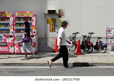 TOKYO, JAPAN - May 17, 2019: A sidewalk in Tokyo's Taito Ward with a pair of drinks vending machines & electric bikes belonging to Toyko's public bicycle sharing scheme.