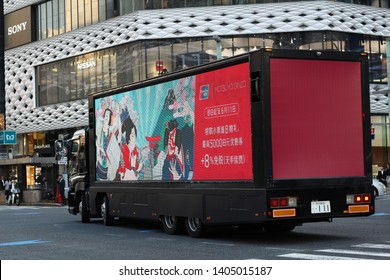 TOKYO, JAPAN - May 17, 2019: An ad truck with a Chinese-language advert for tax-free shopping at Matsuya Department store. It is going through Ginza's 4 Chome junction in front of Ginza Place.