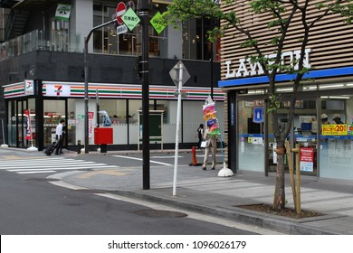 TOKYO, JAPAN - May 19, 2018: Modern convenience stores run by rival major chains Lawson & 7-Eleven face each other on opposite sides of a small junction in Ginza, central Tokyo.