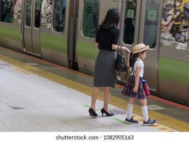 TOKYO, JAPAN - MAY 1ST, 2018. Young Japanese school girl with her mother at Shibuya Railway Station platform.